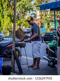 On October 14, 2019 in Jombang, East Java, Indonesia at 03.00pm, I photographed a satay seller on the side of a city road, he was burning the satay