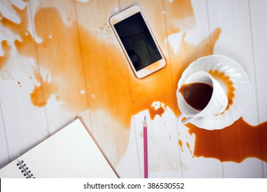 On office desk ,Coffee spilled on mobile phone (concept for working hard, clumsy or repair service)