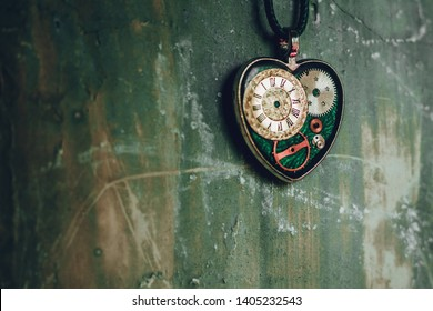 on the old ancient wall there is a pendant in the shape of a heart on a rope, and inside it is an old clock mechanism; concept photo show that there is always time for love