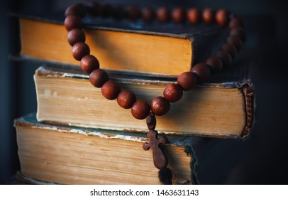 On the old battered Holy Scriptures hang rosaries from beads of red wood, like a Holy relic