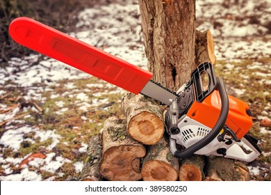On one of the branches of felled trees is a modern and powerful chainsaw.