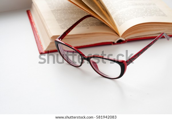 On the open book glasses lie on a light background