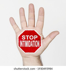 On the palm of the hand there is a stop sign with the inscription - STOP INTIMIDATION. Isolated on white background.