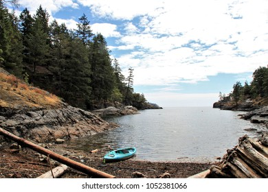 On a party cloudy, partly sunny day a turquoise kayak lays at the shoreline on a rocky, driftwood beach surrounded by a beautiful calm inlet of water and evergreen trees.