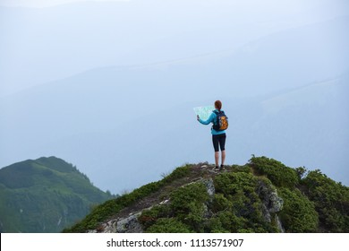 On the peak of the mountain the touris girl with the map and compass is searching for the way to dream. The horizon in the fog. Summer scenery. Extreme sport. Location the Carpathian Mountains.