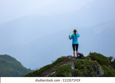 On the peak of the mountain the touris girl with the map and compass is searching for the way to dream. The horizon in the fog. Summer scenery. Extreme sport.