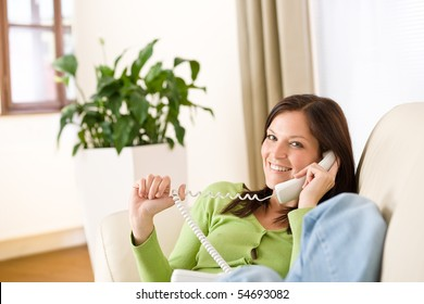 On the phone home: Smiling woman calling in lounge, plant in background
