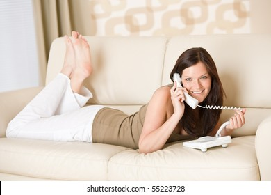 On the phone: young woman calling in lounge, lying down on sofa