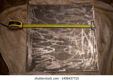 on the photo is a metal plate with carbines and a tape measure