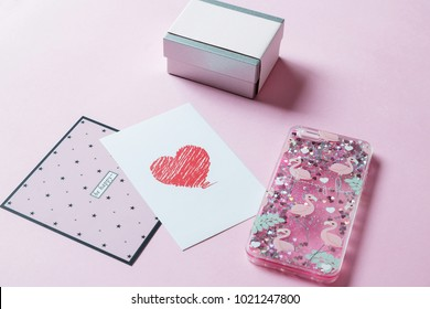 "on a pink background flat lie: a gift box, a case for phone and cards with the inscriptions ""be happy"", ""red heart"""