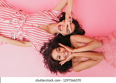 On pink isolated background beautiful dark-skinned girls with cute smiles are having fun and posing in front of camera lying on their backs