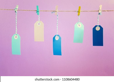 On the pink photographed labels. Five multicolored empty labels hang on a rope pinned with clothespins. Bright layout mock up.