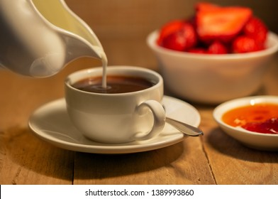 On a plank table in a white Cup with coffee from a white milkman pouring milk in a white bowl of red strawberries in a saucer of jam.
