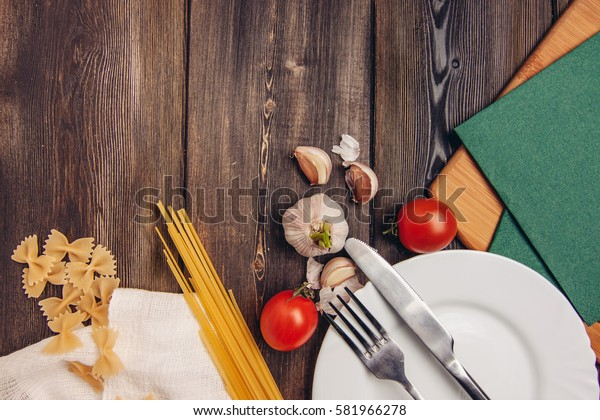 on a plate with a fork and nozh.pasta farfalle, spaghetti, cherry tomatoes, wooden paddle for frying.