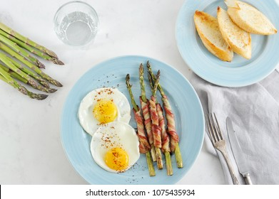 On a plate of fried eggs and asparagus in bacon. Next to the plate is a fried baguette. In the frame a glass with water, fresh asparagus and cutlery. Light background. View from above.