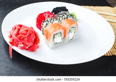 on the plate is white, lined with different rolls, sushi, Red, black, Philadelphia sesame