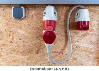 On a pressboard mounted 220 volts and two 380 volt sockets in a factory hall, red and white