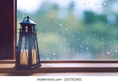 On a rain day, see the water drops on the outside mirror blurred. (window background) Candle holder occupied by the window.  Feelings, sadness, loneliness, nostalgia.