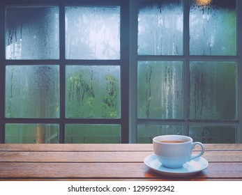 On a rainy day, see the water drops on the outside mirror blurred. (a rainy day window background) And on the table there is a white coffee cup on the right side. Feelings, sadness, loneliness
