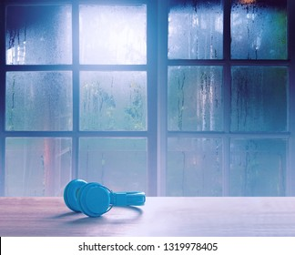 On a rainy day, see the water drops on the outside mirror blurred. (rainy day window background) On table, there is a headphone for opening music on the left. Feelings, sadness, loneliness, nostalgia.
