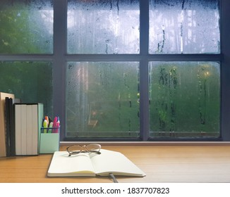 On a rainy day, see the water drops on the outside mirror blurred. (a rainy day window background) On the table there are glasses, diaries, books, pens and notebooks on the left.