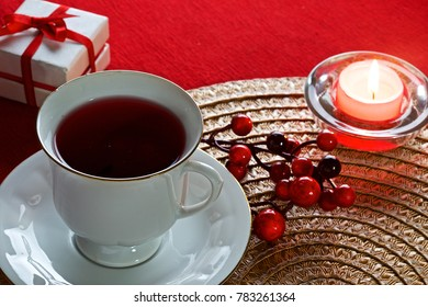 on a red background and a decorative napkin there is a mug with tea, ornaments and a gift