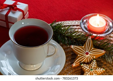 on a red background and a decorative napkin there is a mug with tea, Christmas gingerbread, a candle, ornaments and a gift