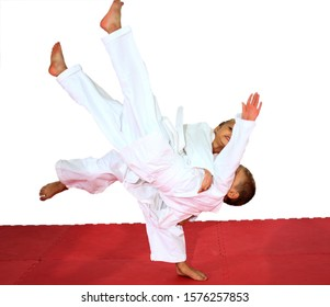 On a red tatami girl and boy are training judo throws