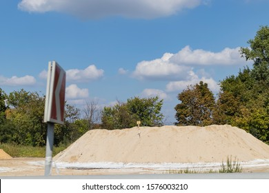 On the road lies a pile of sand, an integral part of the construction industry, building materials of prime necessity, a component for the glass industry, construction of real estate and road works.
