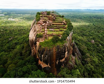 on a rock mountain are many tourism with green tree and mountain surrounded by dense green trees forest in outdoor park