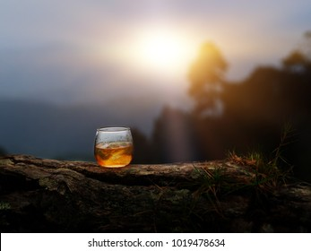 On the rock of whiskey put on nature wood in the evening time with flair from sunset