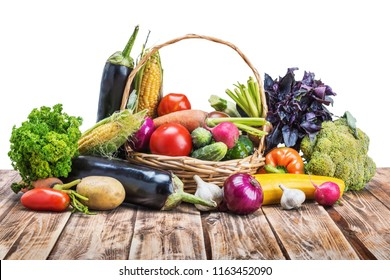 On the rustic wooden table in the basket and next to it lie the vegetables. Isolated on white background.