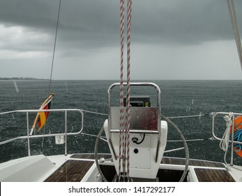 On a sailing yacht off the south coast of Sweden near the town Karlskrona. It is raining and the weather is uncomfortable. There are dark clouds in the sky and the cockpit is wet.