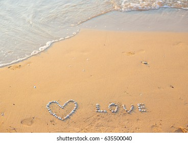 On the sand shells lined with heart and the word love