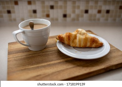 Сroissant on a saucer and a cup of morning coffee on a wooden board. Image with selective focus.