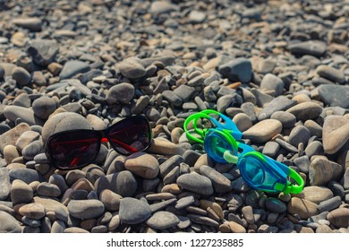 On the seashore,  glasses for swimming and  glasses goggles from sunlight lie on the stones. The concept of relaxing on a pebble beach on a sunny day. Sea pebbles at the seashore - spa procedures.