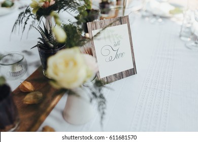On the served buffet table there is a card with the number of the table, beside on wooden supplies there are compositions of flowers in glass vases