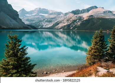 On a shore of glacial turquoise lake with mountains reflection during autumn