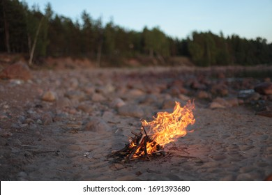 On the shore of the lake, a kettle hangs over a fire and boils. A backpack stands nearby.