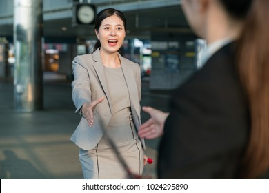 On a side view. Asian business women meet and greet when they first meet. They are going to attend a meeting.