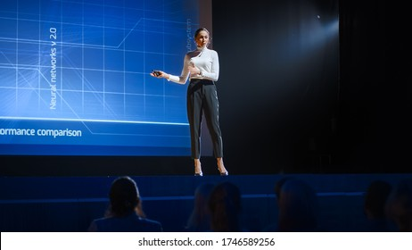 On Stage: Inspirational Female Speaker, Talking about Happiness, Self, Success, Efficiency, Health, and How to Be More Productive. Tech Industry Business Conference Auditorium Hall full off People