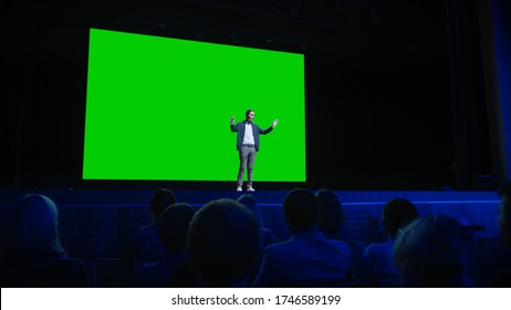 On Stage, Keynote Speaker Presents New Product to the Audience, Behind Him Movie Theater with Green Screen, Mock-up, Chroma Key. Business Live Event or Device Reveal