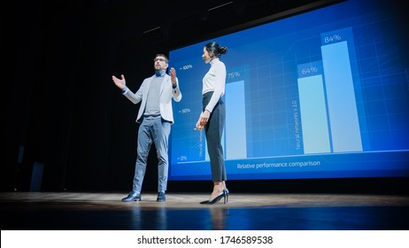 On Stage, Successful Female CEO and Male COO Speakers Present Company's New Product, Show Infographics, Statistics on Big Screen, Talk About Growth. Live Event, Tech Startup, Business Conference - Shutterstock ID 1746589538