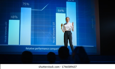 On Stage, Successful Female Speaker Presents Technological Product, Uses Remote Control for Presentation, Showing Infographics, Statistics Animation on Screen. Live Event  Device Release.
