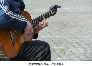 On the street a man plays the guitar
