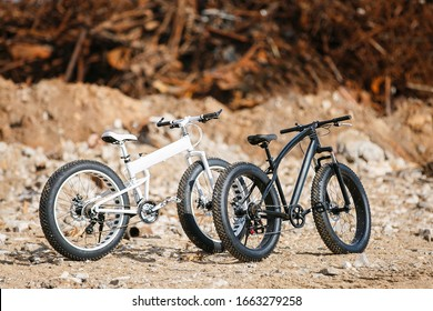 On the street on the stones are two large off-road two-wheeled bicycles with male Fat bike frames. One is completely black, the second is two-tone white with black wheels