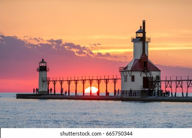 On the Summer Solstice, the sun sets on Lake Michigan between the Inner and Outer North Pier Lighthouses at St. Joseph, Michigan.