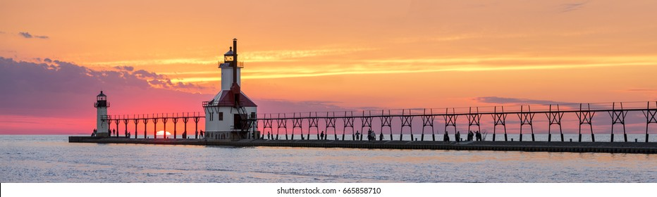 On the Summer Solstice, the sun sets on Lake Michigan between the Inner and Outer North Pier Lighthouses at St. Joseph, Michigan. The lights, catwalk, and people are silhouetted by an dramatic sunset.