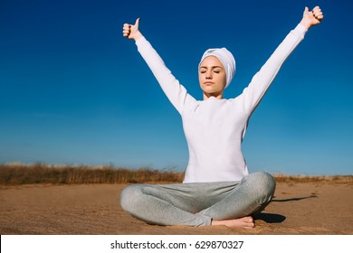 On a sunny afternoon in the sand a girl in white clothes is sitting and practicing yoga, relaxation, kundalini