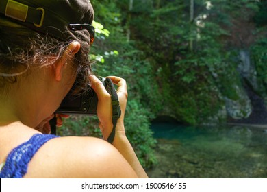 On a sunny day, close shot from the back of a woman taking a photo of la source bleue in Doubs, France, blurred background